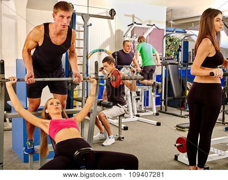 Women and men hard working  on different  simulator at gym. She lifting barbell.