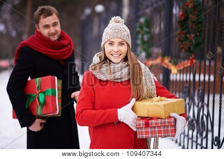 Smiling woman standing with gift boxes with man behind her