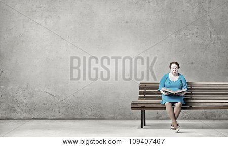 Plus size woman with book in hands sitting on bench