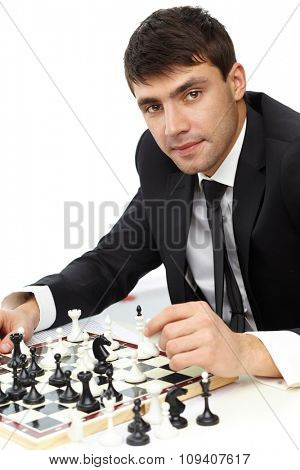 Young businessman playing chess solo on white background