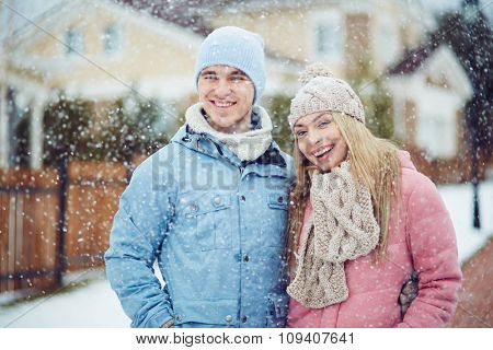 Winter young couple standing while snowing