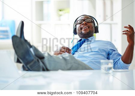 Businessman listening to music in headphones at office