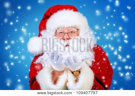 Good old Santa Claus blowing a snow over blue background. Snowfall, snowflakes. The magic of Christmas.