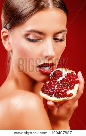 Attractive young woman eating fresh pomegranate. Sexual lips, red lipstick. Healthy food concept. Red background.