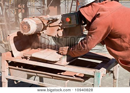 Worker Cutting Red Brick