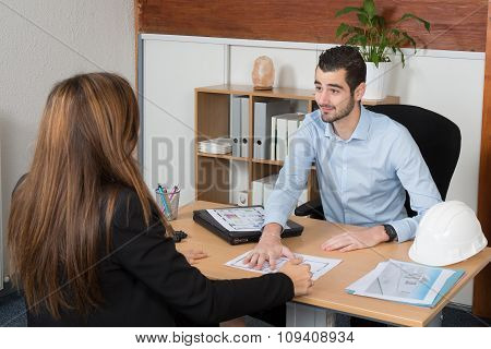 An Adviser Sitting In A Meeting On The Table Explaining Something His Colleague.