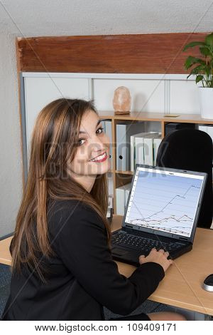 Young And Happy Business Woman Sitting At Desk And Working. Smiling And Looking Back At Camera