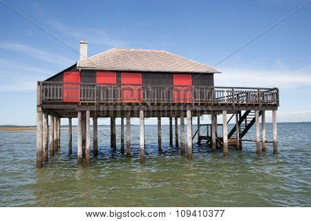 Wooden Tropical Home On Stilts Over Water Of The Sea