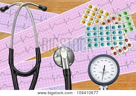 Blood Pressure Meter, Digital Tablet, Pills And Stethoscope On Wooden Table