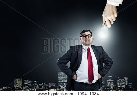 Middle-aged businessman looking at glass glowing lightbulb