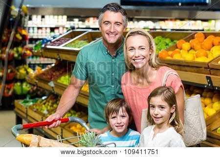 Young Family posing together with trolley at supermarket