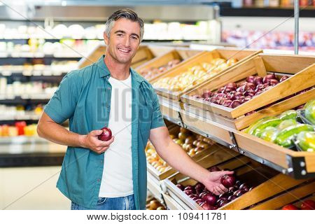 Smiling man choosing a onion at supermarket