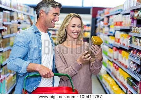 Smiling couple looking for coffee at supermarket