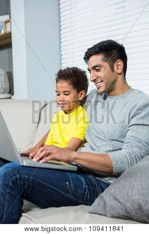 Smiling father and son using laptop on the sofa in living room