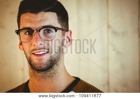 Handsome hipster posing for camera on wooden background