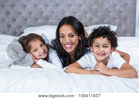 Portrait of smiling mother with children on the bed