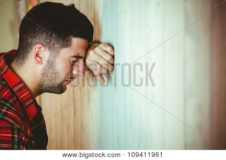 Stressed man leaning against wooden wall