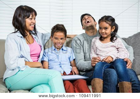 Smiling family using tablet on the sofa in living room