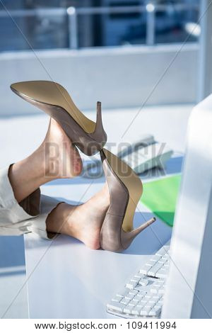 Businesswoman with her legs on her desk in work