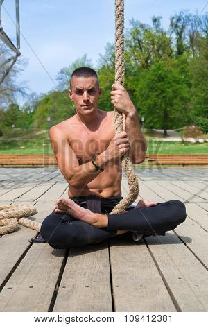 Young shirtless athlete man sitting on the plank floor holding the rope.