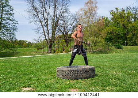 Young athlete man training in the park with sledgehammer and truck tire.