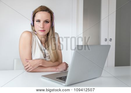 Attractive blonde woman with headset and laptop posing for the camera.