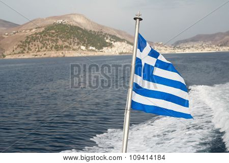 Greek national flag at sea waves and island background