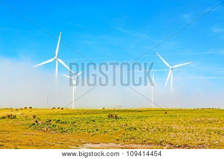 Wind Turbines In Natural Green Landscape - Blue Sky