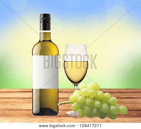 Bottle Of White Wine, Glass And Green Grape On Wooden Table Over Nature Background
