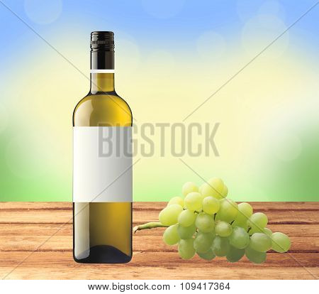 Bottle White Wine And Green Grape On Wooden Table Over Nature Background