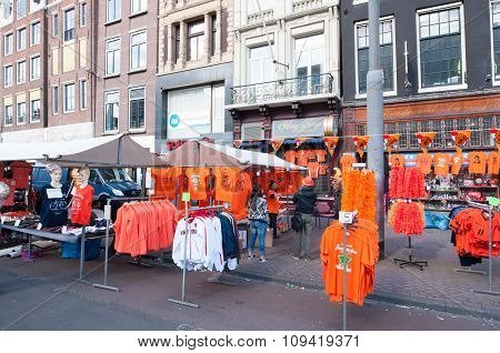 AMSTERDAM-APRIL 27, 2015: Locals display their goods for sale in traditional orange colour on Rokin during the King's Day in Amsterdam. Rokin is a major street in Amsterdam the Netherlands.