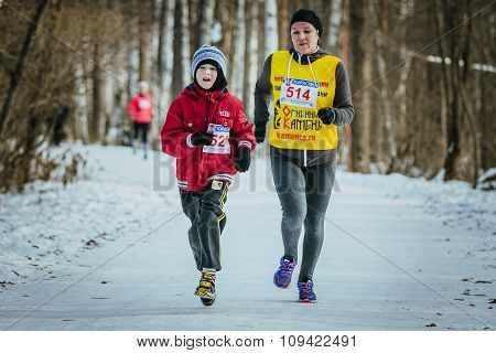 family, a son and mother run together winter woods