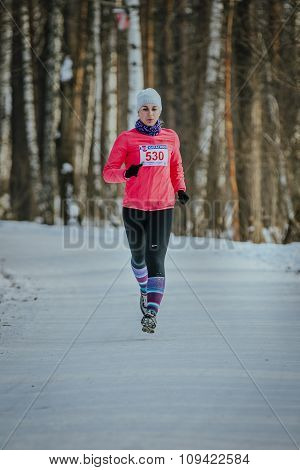 young woman trail running in winter forest