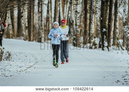 grandson and his grandmother running through winter woods together
