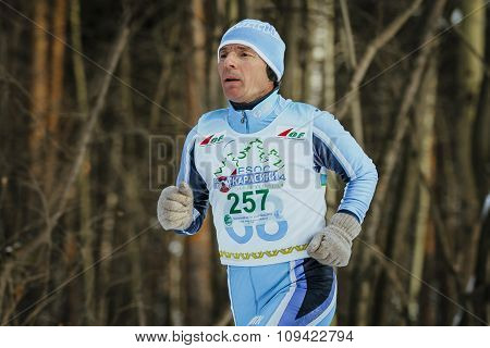 closeup elderly man runner running on track in winter forest