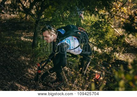 young male athlete in forest is Hiking traill with nordic walking poles