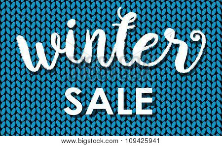 Winter sale. Ink painted  inscription on blue background from knitted wool. Vector illustration.