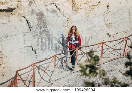 young girl athlete goes on trail along cliff rocks