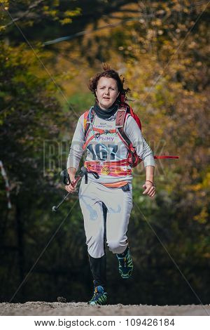 happy young woman running in autumn Park with nordic walking poles