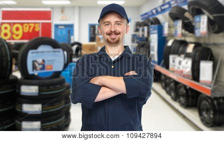 Smiling car mechanic over garage background.