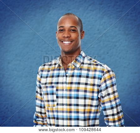 Young smiling African-american businessman over blue background.