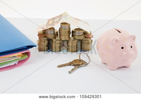 Small House Made With Money And Pink Piggy Bank. Keys And Documents
