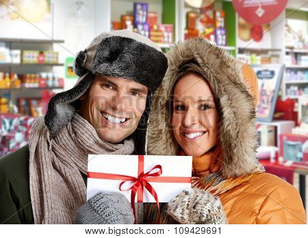 Couple with  envelope Christmas gift over shopping mall background.
