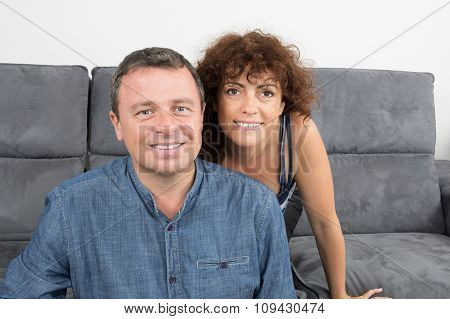 Happy Couple Looking At The Camera At Home On Sofa