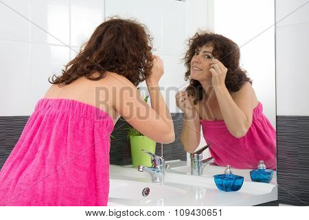 Closeup Of A Smiling Woman Plucking Eyebrow In Her Bathroom