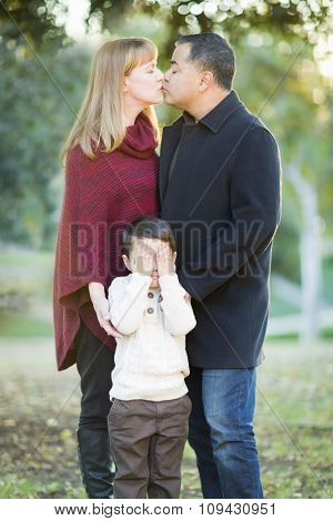 Loving Mix Race Couple Kissing As Young Son Hides His Eyes.