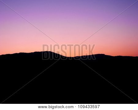 Black Silhouette Of Mountains On Background Of Pink Sunset