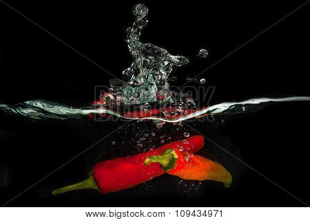 studio picture concept. chili dropped into a container of water to obtain a water splash interesting