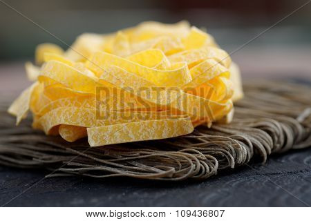 Two types of pasta on a wooden plank
