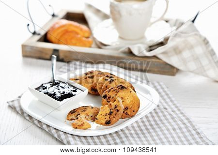 Plate of tasty cookies with chocolate crumbs and jam against cup of coffee on wooden tray